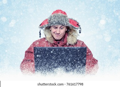 Funny man programmer in red winter clothes with laptop, cold, snow, blizzard