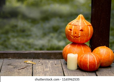 funny man of pumpkins with a carved face on a wooden old floor on the bridge in the autumn mistery Park. Concept for Halloween