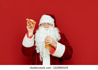 Funny man in santa claus costume isolated on red background with beer bottle and slice of pizza in hands, smiling with eyes closed. Cheerful Santa is having fun under alcohol. Copyspace