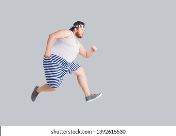 Funny man in striped shorts runs on a gray background.