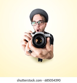 Funny man with a funny surprise expression shooting with his vintage reflex photo camera