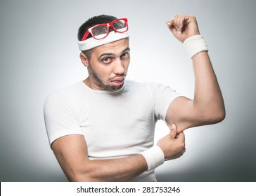 Funny man testing the flabby muscle under her arm - triceps pulling it down with her hand as she checks for muscle tone or weight gain. Nerd sport man