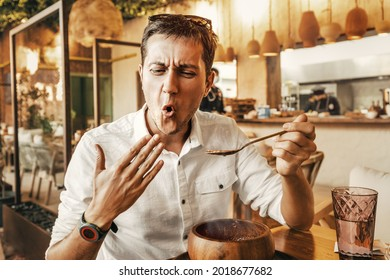 Funny man tries a spicy and hot dish from the national cuisine. He's all red and is trying to cool his mouth with his hand