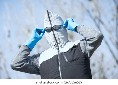 The funny man in vest with hood is wearing sunglasses, protective wear in coronavirus pandemic.