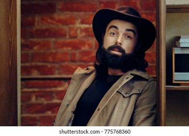 Funny Man Wearing Cowboy hat in western style portrait. Male model wearing rodeo hat having a laid back attitude