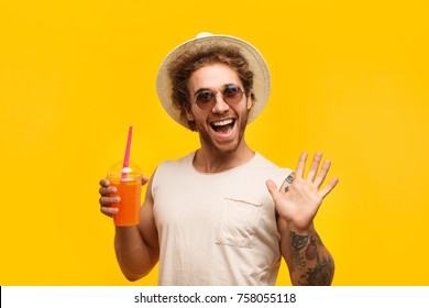 Funny man wearing hat and holding cup of drink.