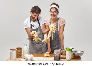 Funny man wears apron, tries to cook pastry, stretches sticky dough, has cooking failure, cheerful housewife stands near, surrounded with baking products on table, try cookies recipe, pose at kitchen