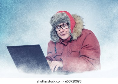 Funny man in winter clothes with laptop, cold, snow.