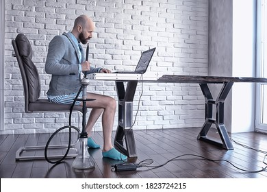 funny man in works at home, smokes a hookah at a remote work, quarantine coronavirus in underpants