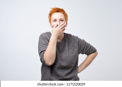 Funny mature woman with short red hair closing her mouth with palm hearing funny joke. Trying not to laugh loudly
