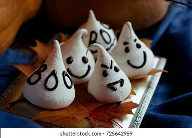 Funny meringue ghosts for Halloween party on autumn decorations. Golden leaves, pumpkin, blue textil and light of candles. Halloween concept