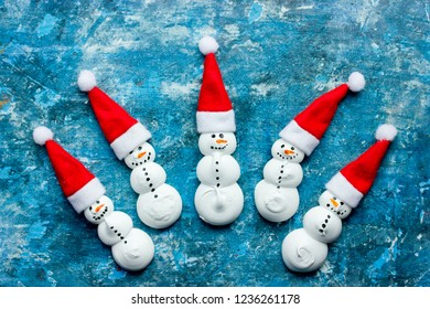 Funny meringue snowman in santa hat, concept New Year and Christmas background