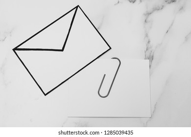 funny metaphor of inbox with email envelop and attachment clip on real-life desk, flatlay shot from topdown perspective