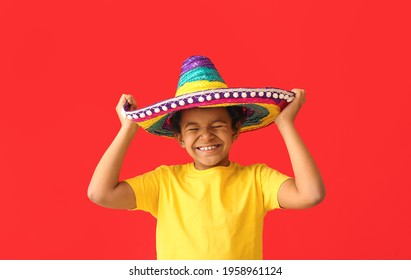 Funny Mexican boy in sombrero hat on color background