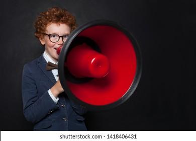 Funny mischievous child boy speaking through a loudspeaker on blackboard background. Kid with red megaphone