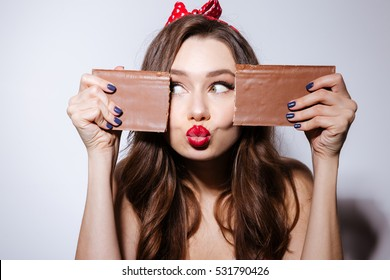 Funny model in underwear playing with chocolate and sands air kiss. As well as looking away. Isolated gray background