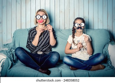 Funny mom and daughter with false mustaches, playing at home