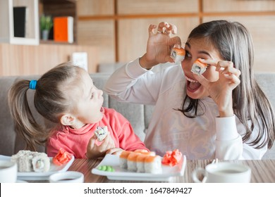 Funny mom with daughter holding sushi rolls in front of eyes