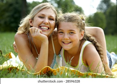 Funny mom and daughter smiling outdoors