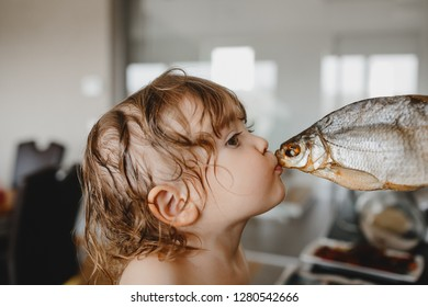 Funny moments, baby portrait. Little kid with adorable wet curls kisses salted fish