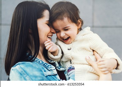 Funny mother and daughter play together and walking along city street. Good relationship of parent and child. Happy family moments of mom and toddler. Childhood and motherhood care.