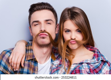 Funny moustache. Beautiful young loving couple making fake moustache from hair while standing against grey background