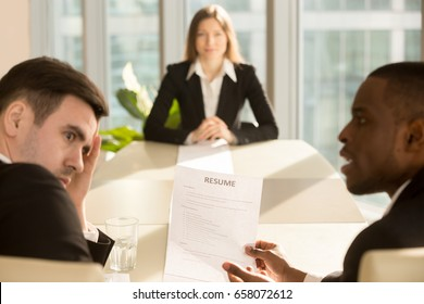 Funny multiethnic employers impressed by female applicant skills at job interview, black and white recruiters considering candidate shocked by great career achievements or bad poor cv, focus on resume