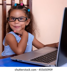 Funny multiracial small girl wearing glasses and using a laptop computer at home