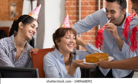 Funny multiracial work team have fun congratulate smiling female colleague present tasty birthday cake, excited diverse workers surprise coworker make office party celebrating anniversary at workplace