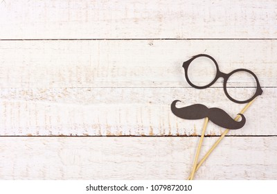 Funny mustache and glasses on sticks against a rustic white wood background. Top view with copy space.