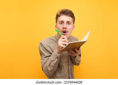 Funny nerd in glasses and shirt looks surprised at the camera and writes in a notebook on a yellow background. Portrait of funny student writes in exercise book, isolated.