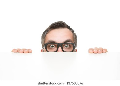 Funny nerd peeking from behind the desk isolated on white background with copy space