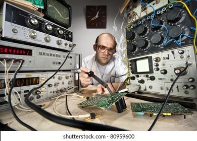 Funny nerd scientist soldering at vintage technological laboratory