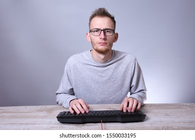 Funny nerd young businessman, man working on computer.Typing on the keyboard programmer in glasses in front of computer.