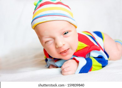 Funny Newborn Baby Lies Lie on stomach, smiles and winks