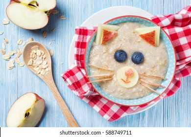 Funny oat porridge with cat, kitten face made of fruit and berries, food for kids idea, top view