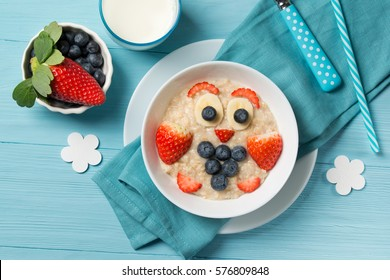 Funny oat porridge with owl face made of berries, food for kids idea, top view