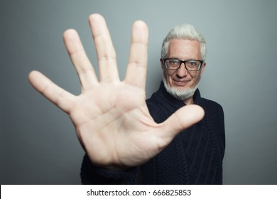 Funny old hipster concept. Portrait of 60-year-old man standing over gray background and giving five. Close up. Studio shot
