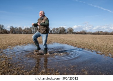Funny old man jumps with rubber boots through the puddle on the meadow and is happy about the first beautiful sunny day after the long winter.