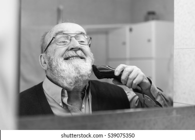 funny old man shaving his long beard with electric razor