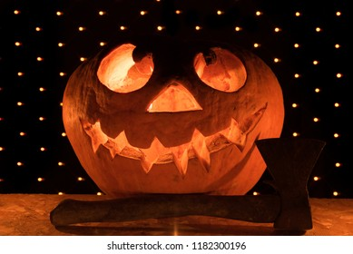 A funny orange pumpkin like a head with carved eyes and a smile with burning candles and an ax on a black background with a garland for the Halloween party