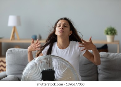 Funny overheated woman enjoying fresh air, cooling by electric fan, exhausted young female waving hands, sitting on couch at home in front of ventilator, suffering from hot summer weather