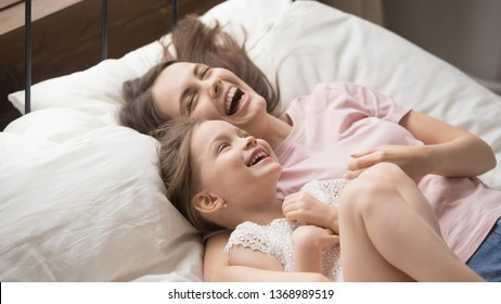 Funny overjoyed sisters having fun on weekend lying in bed in the morning on soft pillows laughing feels happy, mother and daughter enjoying time together. Leisure activities indoors with kids concept