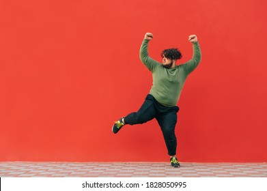 Funny overweight dancer listens to music on headphones and dances on a red background, looking away at copy space. The fat man shows a dance performance on a background of a red wall.