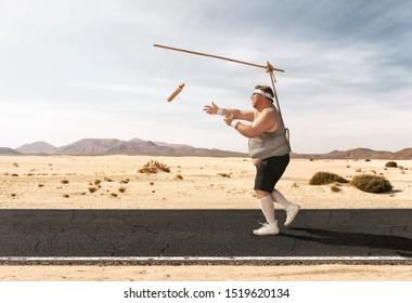 Hombre gracioso con sobrepeso persiguiendo al perro caliente en el palo a través del camino vacío con espacio para copiar