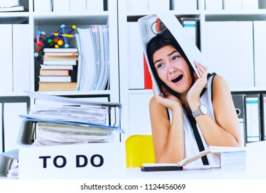 Funny overworked girl with a folder on her head sitting in the workplace cluttered with folders. Reaction of a subordinate when the boss orders her to do too much.