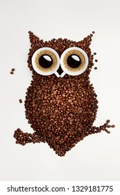A funny owl made of roasted coffee beans and two cups. Creative concept photo of owl made of roasted coffee beans and two cups with refreshment espresso caffeine drink beverage on white background.