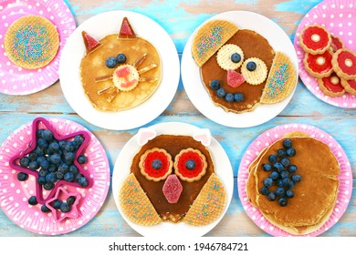 Funny pancakes for children. Cat, dog and owl shaped pancakes on white plates, blue wooden background, top view. Creative idea for kids breakfast
