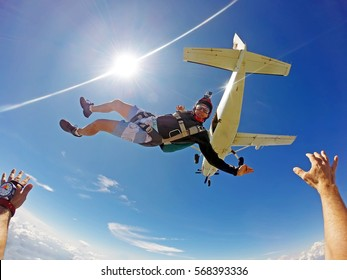 Funny parachutist jumps from an airplane on a summer day. Point of view