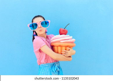 Funny Party Girl with Big Sunglasses and Huge Cupcake. Cute woman wearing silly glasses holding huge cake